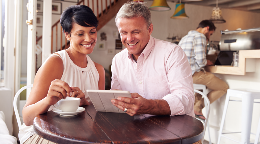 Mature couple looking at tablet in coffee shop