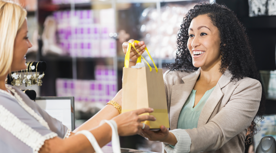 Young female cashier handing female shopper her bag