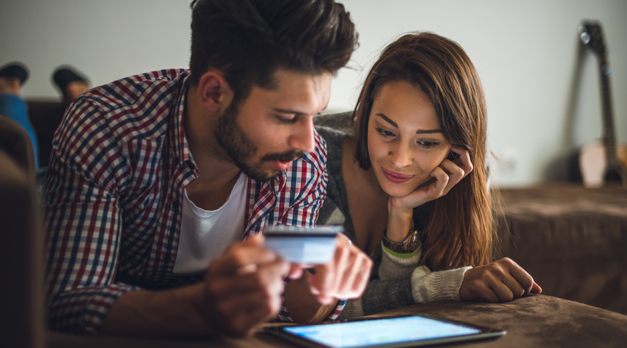 Young couple using debit card to pay for online purchase via tablet