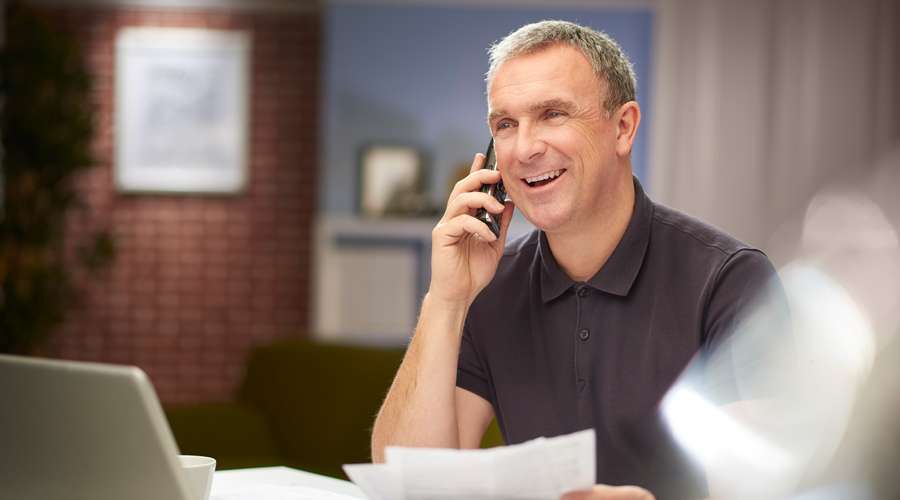 Mature male reviewing bank statements while on the phone
