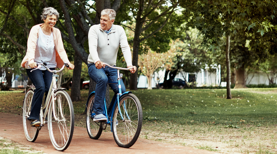 Mature couple riding bike through park
