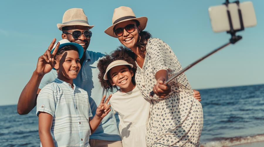 Family of four taking selfie on beach