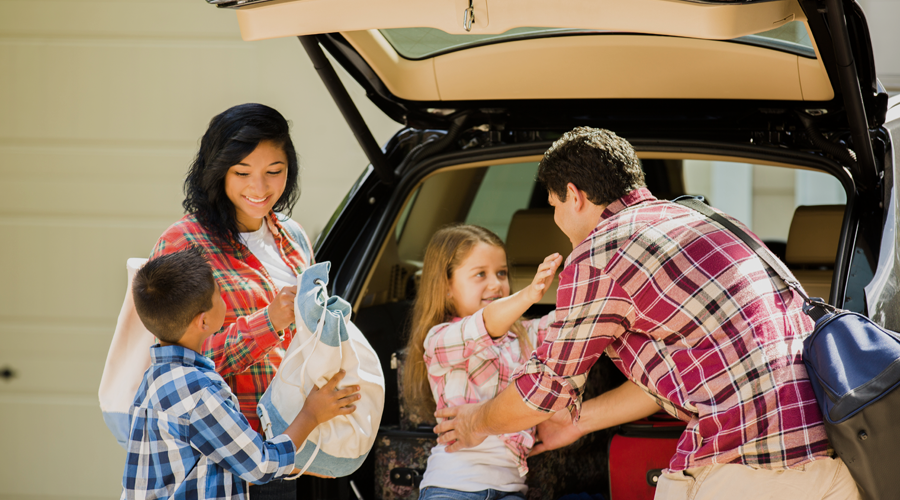 Family of four packing car for vacation