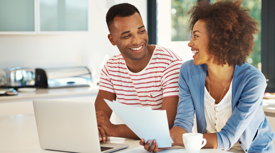 Happy, young couple reviewing paperwork and using laptop