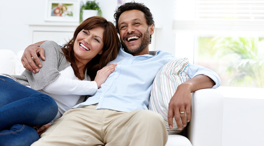 Middle-Age Couple Laughing on Couch