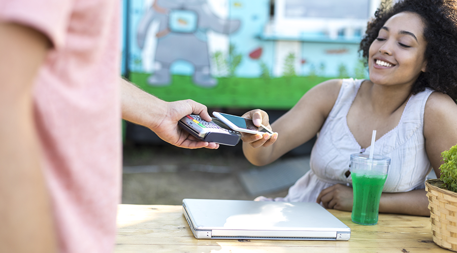 Young lady using mobile phone to make payment