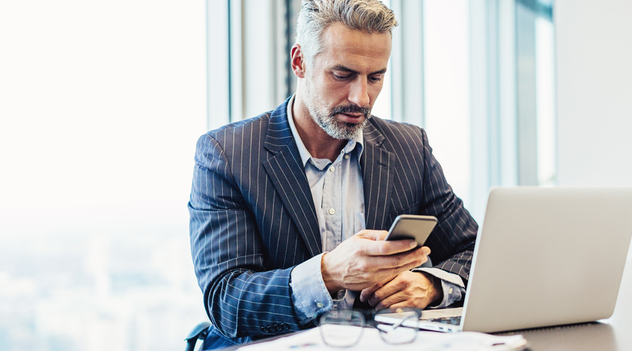 Mature professional male checking account via mobile phone