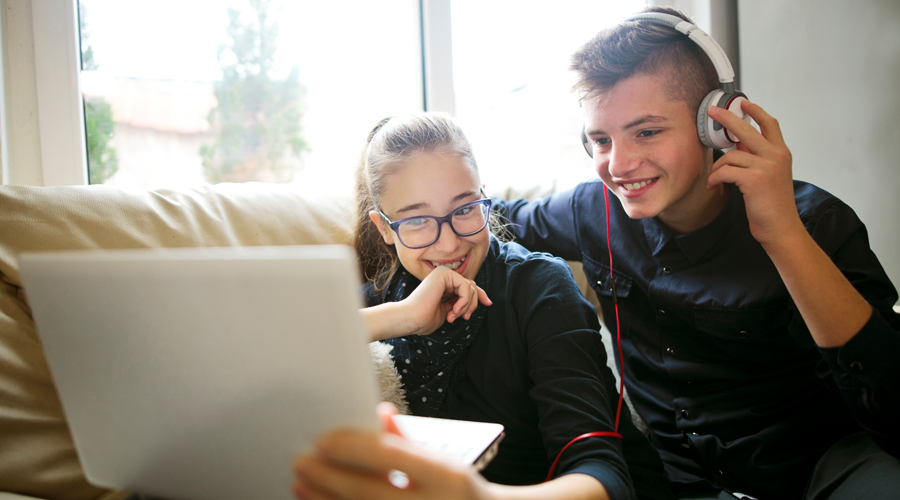 Two Kids Listening to Music and Using a Laptop