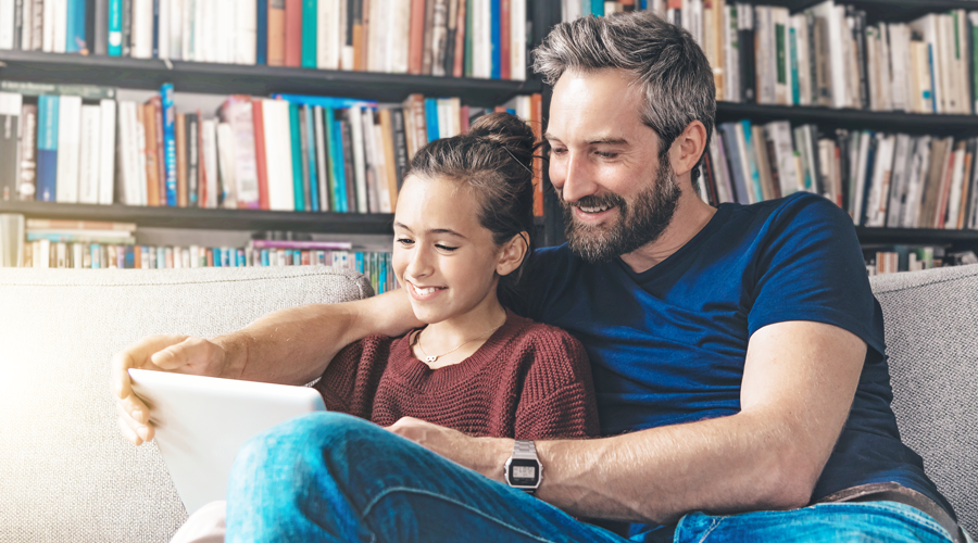 Father and Daughter using Tablet on Couch